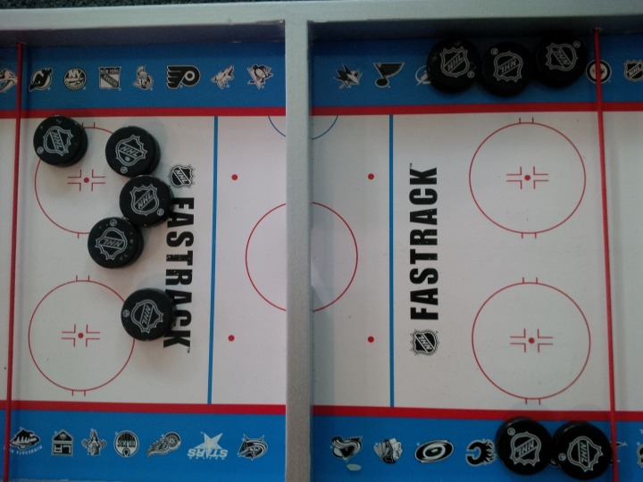 What the board looks like after over 50 plays (after a little quick-and-easy cleanup with a magic eraser). You can see specks where the coating on the pucks is starting to come off, but the logos are holding up well.